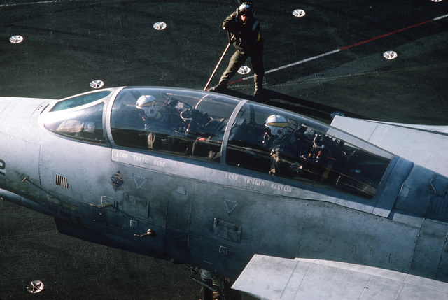 Naval Air Reserve Fighter Squadron 302 (VF-302) flight crew members inspect the cockpit of an F-14A Tomcat aircraft during carrier qualifications aboard the aircraft carrier USS CONSTELLATION (CV 64)