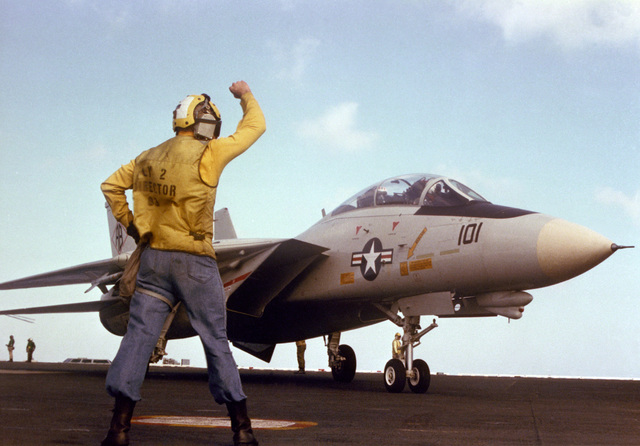 A plane director signals instructions to the pilot of an F-14A Tomcat aircraft during flight operations aboard the nuclear-powered aircraft carrier USS THEODORE ROOSEVELT (CVN-71)