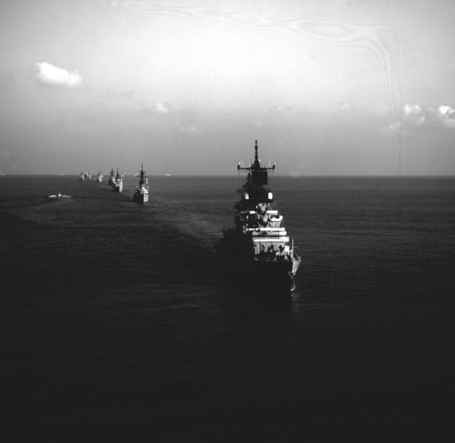 A starboard bow view of the guided missile cruiser USS BELKNAP (CG-26) underway with escort ships of the aircraft carrier USS JOHN F. KENNEDY (CV-67) and nuclear-powered aircraft carrier USS NIMITZ (CVN-68) battle group