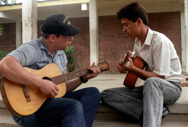 A crewman from the battleship USS IOWA (BB-61) and a local villager compare guitar techniques. The sailor is ashore to take part in a civic action program