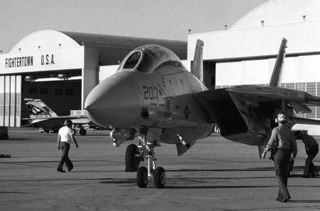 Airmen inspect a Fighter Squadron 2 (VF-2) F-14A Tomcat aircraft parked on the flight line. The aircraft is the first to be transferred from VF-2 to Fighter Squadron 194 (VF-194)