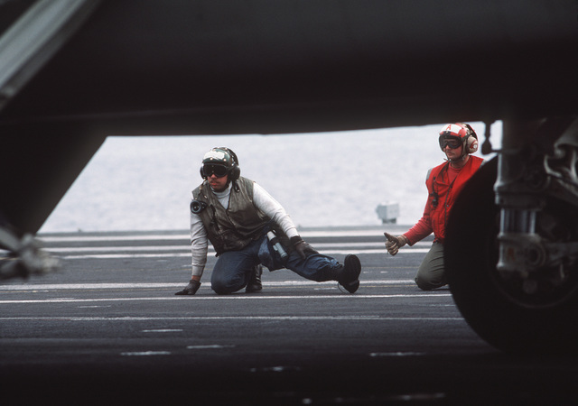 A catapult and arresting gear crewman and an aviation ordnanceman crouch on the flight deck prior to the launch of an aircraft aboard the nuclear-powered aircraft carrier USS THEODORE ROOSEVELT (CVN 71)