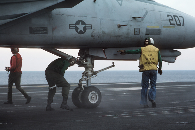 A catapult safety observer watches as a catapult and arresting gear crewman attaches launching equipment to the nose gear of an F-14A Tomcat aircraft during flight operations aboard the nuclear-powered aircraft carrier USS THEODORE ROOSEVELT (CVN 71)