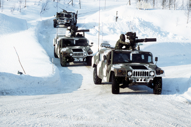 A convoy of M-998 series multipurpose-wheeled vehicles proceeds through the Norwegian countryside during Operation Cold Winter '87, a NATO-sponsored military exercise. The first two vehicles are equipped with Tube-launched, Optically tracked, Wire-guided (TOW) anti-tank weapons systems and the third has an M-2.50-caliber machine gun