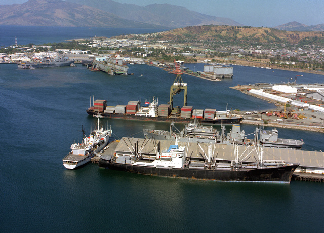 An aerial view of four Military Sealift Command ships moored at the Naval Supply Depot. They are, from top to bottom, the container ship PRESIDENT KENNEDY, the combat stores ship USNS SPICA (T-AFS-9), the surveying ship USNS CHAUVENET (T-AGS-29), and the cargo ship SANTA JUANA (T-AK-1047)