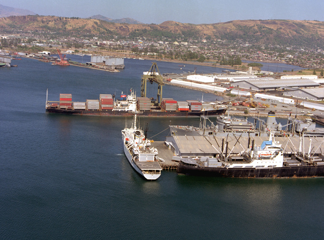 An aerial view of four Military Sealift Command ships moored at the Naval Supply Depot. They are, clockwise from the top, the container ship PRESIDENT KENNEDY, the combat stores ship USNS SPICA (T-AFS-9), the cargo ship SANTA JUANA (T-AK-2047), and the surveying ship USNS CHAUVENET (T-AGS-29)