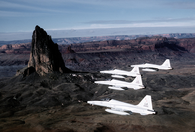 An air-to-air left side view of a flight of four F-5 Talon fighters flying in a finger-tip formation over Monument Valley. Exact Date Shot Unknown