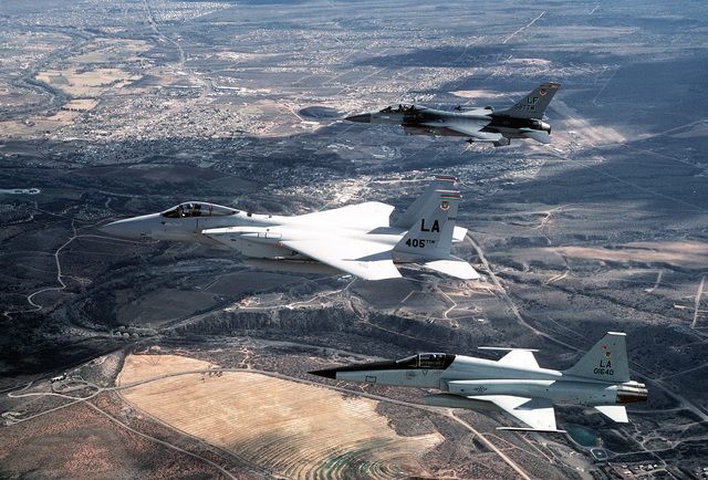 An air-to-air left side view of a flight of three Luke AFB fighters flying in a finger-tip formation. The formation is lead by the F-15 Eagle flagship of the 405th Tactical Training Wing, the F-16 flagship of the 58th Tactical Training Wing on the right wing and an F-5 Talon fighter on the left wing. Exact Date Shot Unknown