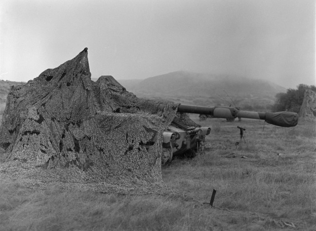 An M109 self-propelled Howitzer is covered with camouflage netting on Red Beach during the amphibious assault Exercise Operation KERNAL BLITZ'87-2