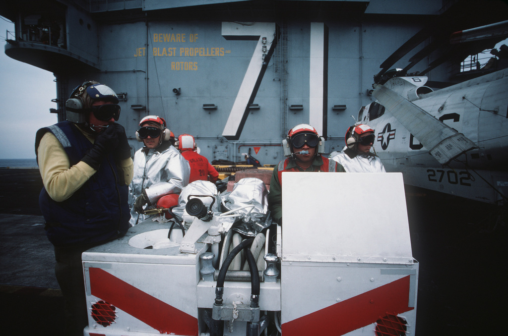 Firefighters wearing proximity suits stand by in a damage control vehicle during flight operations aboard the nuclear-powered aircraft carrier USS THEODORE ROOSEVELT (CVN 71)