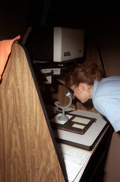Photographer's Mate AIRMAN Michelle Quinn ensures that a negative is in focus before making a set of black and white prints in a darkroom at the Fleet Imaging Center facility
