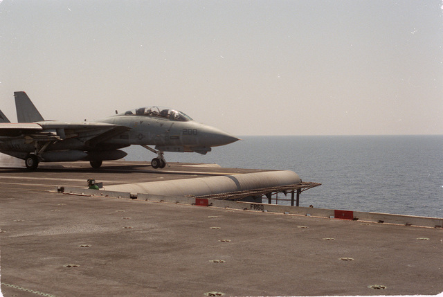An F-14A Tomcat aircraft is launched during flight operations aboard the aircraft carrier USS KITTY HAWK (CV 63)