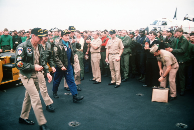 Officers and crewmen applaud after listening to an address by Secretary of the Navy John F. Lehman Jr. on the flight deck of the aircraft carrier USS JOHN F. KENNEDY (CV 67). The carrier's return to home port has been delayed because of events in Lebanon