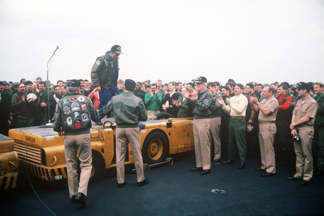 Secretary of the Navy John F. Lehman Jr. steps down from an MD-3A tow tractor after addressing officers and crewmen gathered on the flight deck of the aircraft carrier USS JOHN F. KENNEDY (CV 67). The carrier's return to home port has been delayed because of events in Lebanon