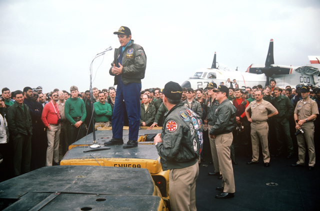 Secretary of the Navy John F. Lehman Jr. uses an MD-3A tow tractor as a podium while addressing officers and crewmen gathered on the flight deck of the aircraft carrier USS JOHN F. KENNEDY (CV 67). The carrier's return to home port has been delayed because of events in Lebanon