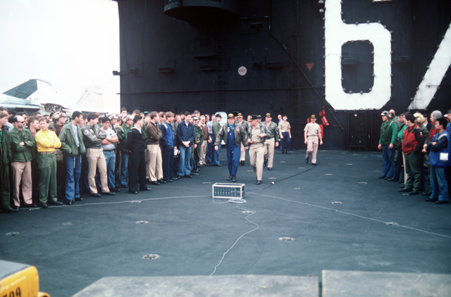 Secretary of the Navy John F. Lehman Jr. walks out onto the flight deck to address officers and crewmen aboard the aircraft carrier USS JOHN F. KENNEDY (CV 67). The carrier's return to home port has been delayed because of events in Lebanon