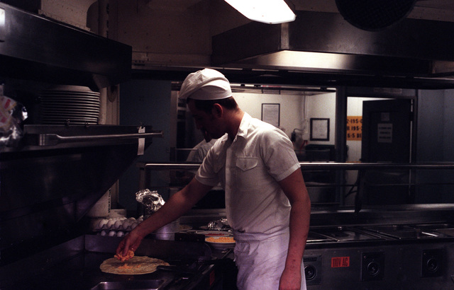 A mess specialist prepares an omlette aboard the nuclear-powered aircraft carrier USS THEODORE ROOSEVELT (CVN 71)