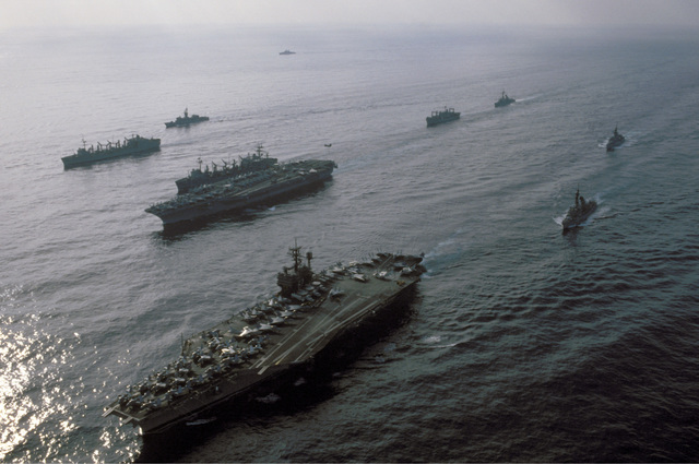 A silhouetted port bow view of the aircraft carrier USS JOHN F. KENNEDY (CV 67), foreground, and the nuclear-powered aircraft carrier USS NIMITZ (CVN 68) and their escorts underway off the coast of Beirut, Lebanon