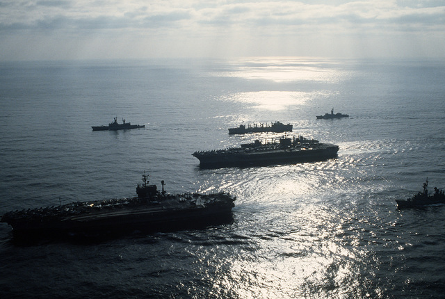 A silhouetted port bow view of the aircraft carrier USS JOHN F. KENNEDY (CV-67), foreground, and the nuclear-powered aircraft carrier USS NIMITZ (CVN-68) and their escorts underway off the coast of Beirut, Lebanon