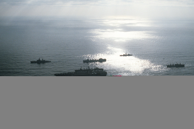 A silhouetted port view of the aircraft carrier USS JOHN F. KENNEDY (CV-67), foreground, and the nuclear-powered aircraft carrier USS NIMITZ (CVN-68) underway off the coast of Beirut, Lebanon, with their escort ships