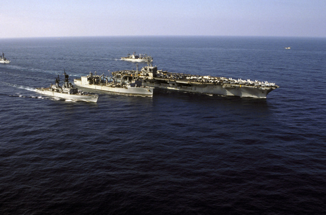 A starboard bow view of the nuclear-powered aircraft carrier USS NIMITZ (CVN 68) participating in an underway replenishment with the replenishment oiler USS KALAMAZOO (AOR 6) while underway off the coast of Beirut, Lebanon. The other ships aescorting the NIMITZ include, left to right: the guided missile destroyer USS RICHARD E. BYRD (DDG 23), the guided missile cruiser USS JOSEPHUS DANIELS (CG 27), and the ammunition ship USS NITRO (AE 23)