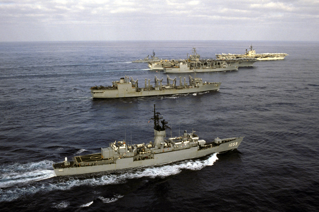 A starboard view of the aircraft carrier USS JOHN F. KENNEDY (CV 67) and the nuclear-powered aircraft carrier USS NIMITZ (CVN 68) and their escorts underway off the coast of Beirut, Lebanon. The escorts are, from front to back: the frigate USS W.S. SIMS (FF 1059) replenishment oilers USS SAVANNAH (AOR 4) and USS KALAMAZOO (AOR 6) and the guided missile destroyer USS RICHARD E. BYRD (DDG 23)