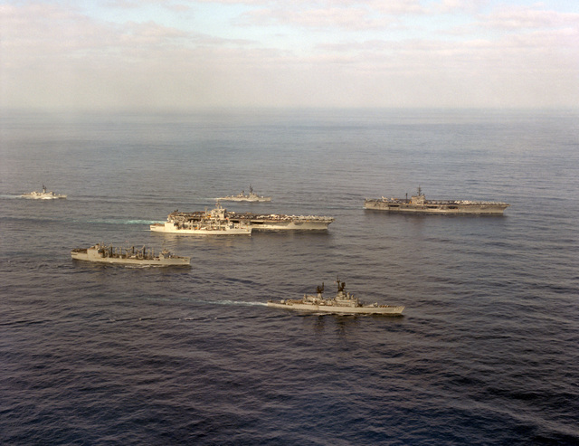 An aerial starboard bow view of Carrier Group Eight underway. They are, from left to right: frigate USS W.S. SIMS (FF 1059), replenishment oilers USS SAVANNAH (AOR 4) and USS KALAMAZOO (AOR 6), nuclear-powered aircraft carrier USS NIMITZ (CVN 68), guided missile destroyer USS BYRD (DDG 23), guided missile cruiser USS JOSEPHUS DANIELS (CG 27) and the aircraft carrier USS JOHN F. KENNEDY (CV 67)