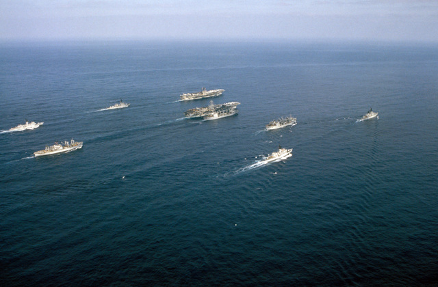 An aerial starboard quarter view of the nuclear-powered aircraft carrier USS NIMITZ (CVN 68), the aircraft carrier USS JOHN F. KENNEDY (CV 67) and their escorts underway off the coast of Beirut, Lebanon. The escorts are, clockwise from left: frigate USS W.S. SIMS (FF 1059), guided missile destroyer USS RICHARD E. BYRD (DDG 23), replenishment oilers USS KALAMAZOO (AOR 6) and USS SAVANNAH (AOR 4), guided missile cruiser USS JOSEPHUS DANIELS (CG 27), the frigate USS TRIPPE (FF F1075) and the ammunition ship USS NITRO (AE 23)