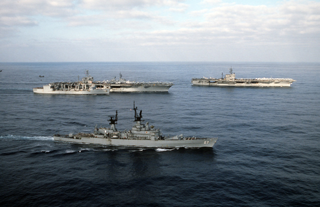 An aerial starboard view of the nuclear-powered aircraft carrier USS NIMITZ (CVN 68) and the aircraft carrier USS JOHN F. KENNEDY (CV 67) underway with escort vessels from Carrier Group Eight. They are the guided missile cruiser USS JOSEPHUS DANIELS (CG 27), foreground, and the replenishment oiler USS KALAMAZOO (AOR 6), starboard of USS NIMITZ