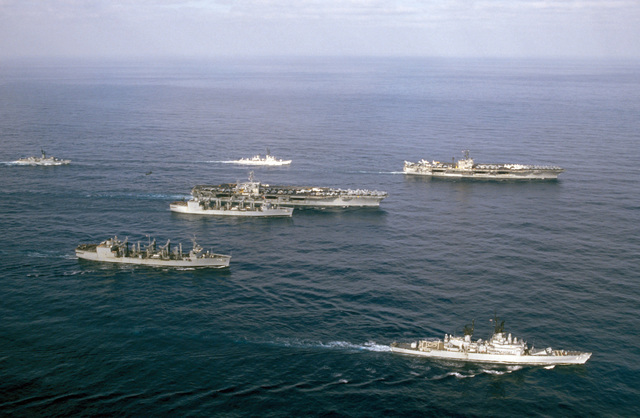 An aerial starboard view of the nuclear-powered aircraft carrier USS NIMITZ (CVN 68) and the aircraft carrier USS JOHN F. KENNEDY (CV 67) underway with their escorts off the coast of Beirut, Lebanon. The escorts are, clockwise from bottom: the guided missile cruiser USS JOSEPHUS DANIELS (CG 27), replenishment oiler USS SAVANNAH (AOR 4), frigate USS TRIPPE (FF 1075), guided missile destroyer USS RICHARD E. BYRD (DDG 23) and the replenishment oiler USS KALAMAZOO (AOR 6)