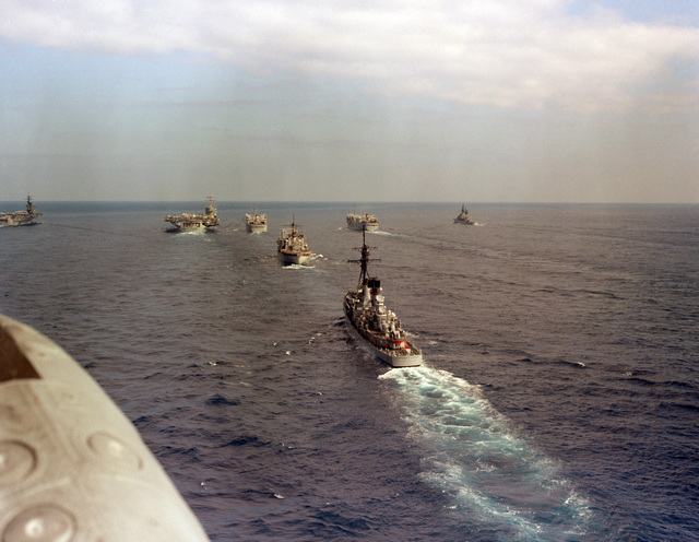 An overall stern view of Carrier Group Eight underway. The ships are, from left to right: aircraft carrier USS JOHN F. KENNEDY (CV 67), nuclear-powered aircraft carrier USS NIMITZ (CVN 68), replenishment ship USS KALAMAZOO (AOR 6), ammunition ship USS NITRO (AE 23), guided missile destroyer USS CHARLES F. ADAMS (DDG 2), replenishment ship USS SAVANNAH (AOR 4) and guided missile cruiser USS JOSEPHUS DANIELS (CG 27). (Substandard image)