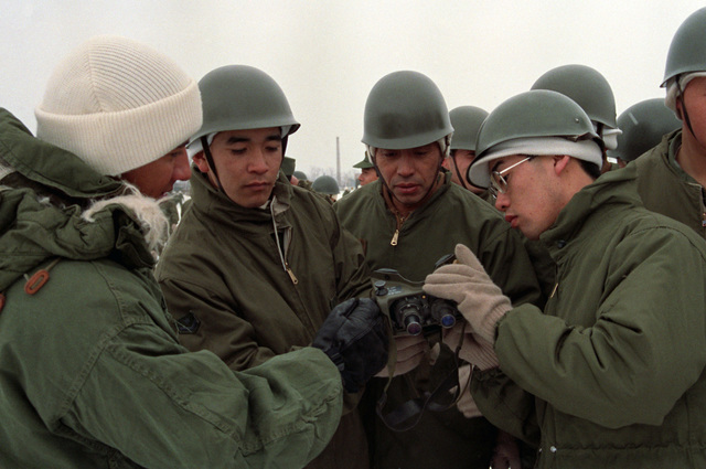 Private First Class (PFC) Darren Smith, left, 3rd Battalion, 22nd Infantry, 25th Infantry Division, explains the operation of a pair of night vision glasses to members of the Japanese Ground Self-Defense Force during Exercise NORTHWIND '87. Members of the 25th Infantry Division are undergoing 23 days of special cold weather training with members of the Japanese Ground Self-Defense Force in the Kotani and Hirosaki Training Area