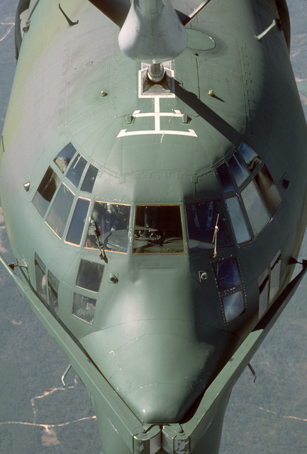 An air-to-air view of an MC-130E Hercules aircraft of the 8th Special Operations Squadron being refueled in flight. The aircraft is equipped with the Fulton recovery system
