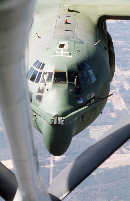 An air-to-air view of an MC-130E Hercules aircraft of the 8th Special Operations Squadron approaching the refueling boom of a tanker aircraft. The aircraft is equipped with the Fulton recovery system