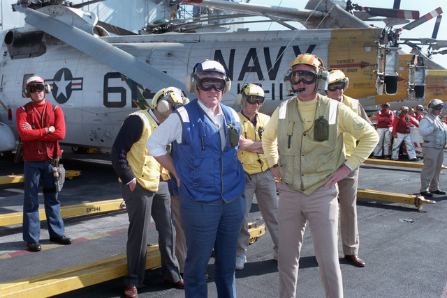 Senator Edward Kennedy, D-Massachusetts, wearing a flight deck helmet and goggles, pauses on the flight deck with Lieutenant Commander Kiety, flight deck officer, and other flight deck crew members during his tour aboard the nuclear-powered aircraft carrier USS THEODORE ROOSEVELT (CVN 71)