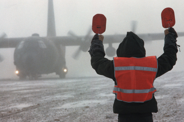 A member of the 616th Military Airlift Group marshals a C-130 Hercules aircraft which has just landed during a combined arms live fire exercise (CALFEX)
