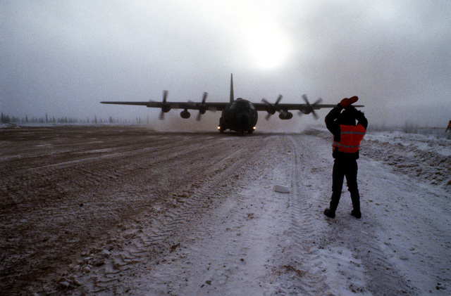 A member of the 616th Military Airlift Group marshals a C-130 Hercules aircraft which has just landed during combined arms live fire exercise (CALFEX). Exact Date Shot Unknown