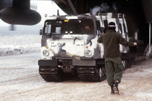 An airman guides an M-973 small unit support vehicle out of a C-130 Hercules aircraft during a combined arms live fire exercise (CALFEX). Exact Date Shot Unknown