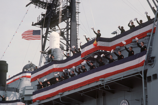 Crew members wave to spectators during a welcoming ceremony for the guided missile cruiser USS MOBILE BAY (CG 53).  The ship has just arrived in Mobile for its commissioning