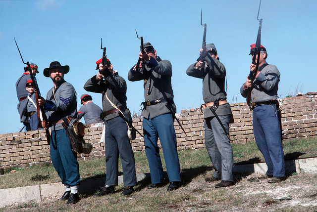 People dressed in Confederate Civil War uniforms participate in a re-enactment of the Battle of Mobile Bay at Fort Morgan.  The re-enactment is one of a series of events celebrating the commissioning of the guided missile cruiser USS MOBILE BAY (CG 53)