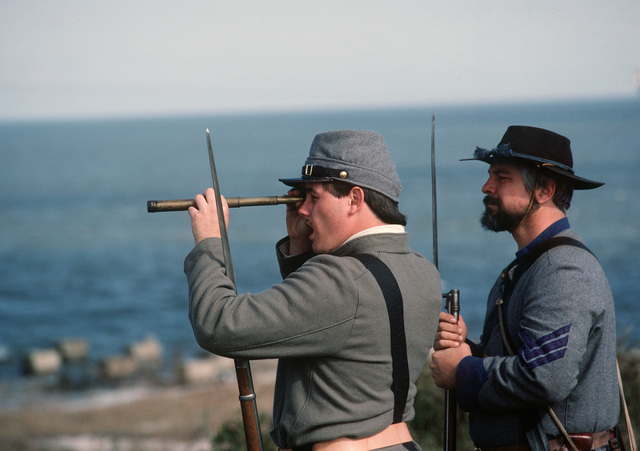 People dressed in Confederate Civil War uniforms scan the horizon for ships during a re-enactment of the Battle of Mobile Bay at historic Fort Morgan.  The re-enactment is one of a series of events celebrating the commissioning of the guided missile cruiser USS MOBILE BAY (CG 53)