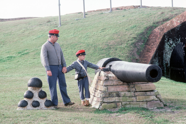People dressed in Confederate Civil War uniforms stand by a cannon at historic Fort Morgan during a re-enactment of the Battle of Mobile Bay.  The re-enactment is one of a series of events celebrating the commissioning of the guided missile cruiser USS MOBILE BAY (CG 53)