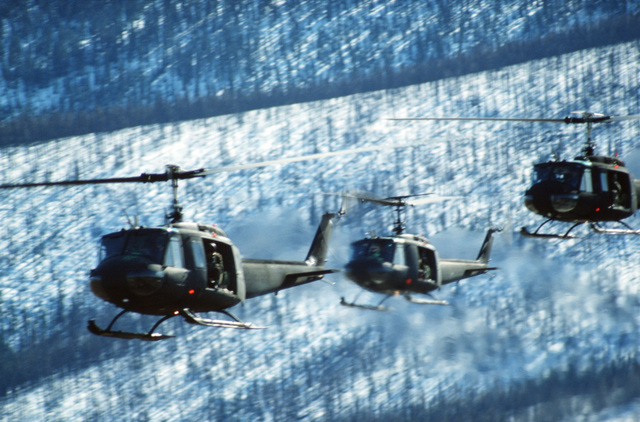 Three UH-1 Iroquois helicopters loaded with troops fly in formation during a combined arms live fire Exercise (CALFEX)