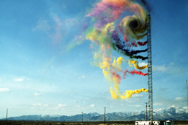 Colored smoke streams from smoke grenades mounted on a 210-foot tower swirls in the wind created by a passing aircraft. Researchers at the Idaho National Engineering Laboratory are investigating the wind vortices created by the passage of an aircraft and the effects that those disturbances would have on low-altitude parachute drops