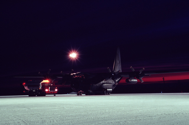 A Canadian Forces CC-130 Hercules aircraft from the 435th(T) Transportation Squadron is refueled in the early morning light at a Canadian Forces base.  The aircraft is resupplying 30 radar stations under US Air Force control on the Distance Early Warning (DEW) Line which runs approximately 3,600 miles, from Alaska, across Northern Canada to Greenland