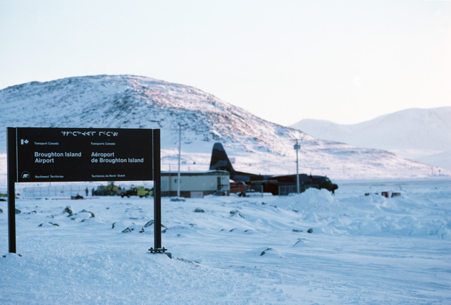 A Canadian Forces CC-130 Hercules aircraft of the 435th(T) Transportation Squadron unloads supplies during a radar station resupply mission along the Distant Early Warning (DEW) Line.  Thirty radar stations are under US Air Force control on the DEW Line which runs approximately 3,600 miles, from Alaska, across Northern Canada to Greenland.  Note the sign, left, written in English, French, and Eskimo