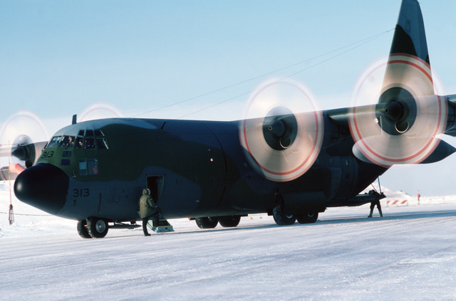Flight engineer Sergeant (SGT) Wolfgang Botin and Loadmaster MCPL Dean Burns make a final check of the outside of their Canadian Forces CC-130 Hercules aircraft from the 435th(T) Transportation Squadron and is on a resupply mission to 30 radar stations under US Air Force control on the Distant Early Warning (DEW) Line which runs approximately 3,600 miles, from Alaska, across Northern Canada to Greenland