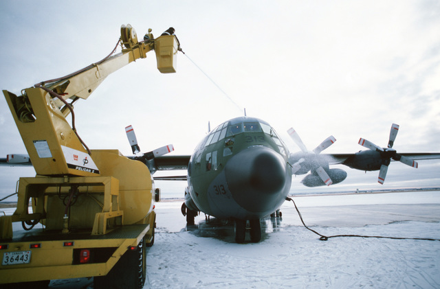 Private Less Hill, Base Aircraft Maintenance Engineering Organization (BAMEO), de-ices a Canadian CC-130 Hercules aircraft from a cherry picker at the 435th(T) Transportation Squadron. The aircraft is being prepared for a resupply mission to 30 radar stations under US Air Force control on the Distant Early Warning (DEW) Line which runs approximately 3,600 miles, from Alaska, across Northern Canada to Greenland