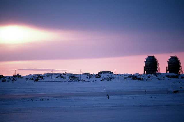 The sun sets behind a radar station. The station is one of 30 under U.S. Air Force control on the Distant Early Warning (DEW) Line which runs approximately 3,600 miles, from Alaska, across Northern Canada to Greenland