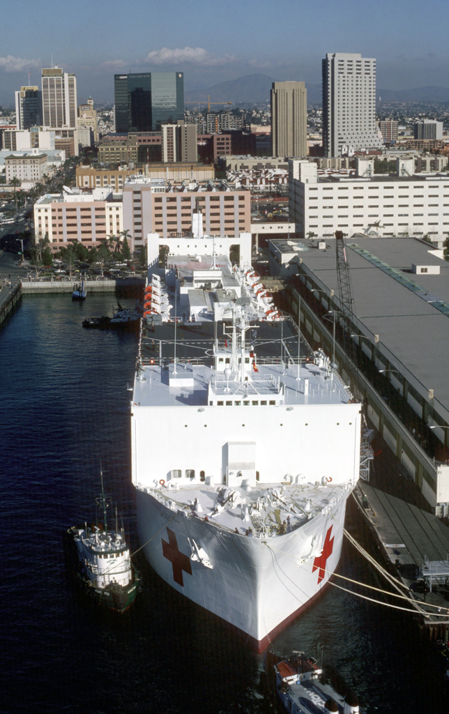 A bow view of the hospital ship USNS MERCY (T-AH 19) moored at the Naval Supply Center pier. The ship is about to depart on its maiden voyage to the islands of the Western Pacific